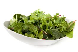 Bowl of mixed salad leaves, isolated on white.